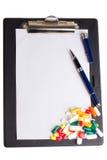 Pillen und Notizblock stockfotografie