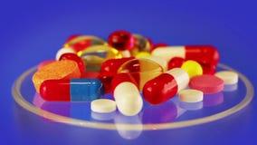 Pillen und Tablettenhaufen, der auf Blau sich dreht stock video