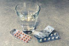 Pillen und Wasser auf Badezimmerwanne Stockfoto