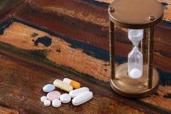 Pillen und Weinlesesanduhr auf Holztisch Lizenzfreie Stockfotos