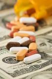 Pillen verschüttet über Geld Stockbild