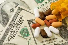 Pillen verschüttet über Geld Stockbilder