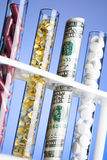 Pillen, Vitamine und Geld in den Reagenzgläsern Stockfotografie