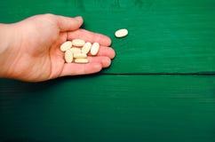 Pillen, vitaminen in een hand op een groene houten achtergrond Concept stock foto