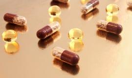Pillen von verschiedenen Formen auf dem goldenen Hintergrund Lizenzfreies Stockbild