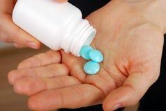 Pillen in vrouwelijke handen Stock Afbeeldingen