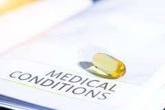 Pillenfarbgelb auf dem Medikationsbuch Stockbild