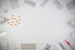 Pillengrenzhintergrund Vitamine, Tabletten und Kapseln, die aus einer Flasche auf weißem Hintergrund heraus verschüttet werden Be Lizenzfreie Stockbilder