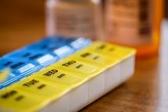 Pillenhalter auf hölzerner Tabelle mit Verordnung füllt Hintergrund ab Stockfotografie