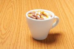 Pillenkapseln des Medikaments in der Kaffeetasse Lizenzfreies Stockfoto