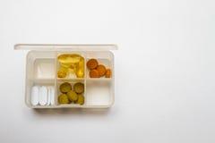 Pillenkasten mit einigen Pillen im Kasten auf weißem Hintergrund Stockfotografie