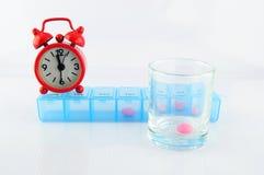Pillenkasten und rosa Tablette im Glas zur Medizinzeit Stockbilder