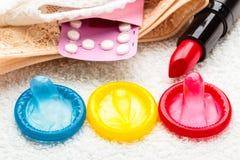 Pillenkondome und -lippenstift auf Spitzewäsche Stockfotografie