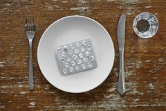 Pillenomslag op de witte geneeskunde van de het supplementapotheek van de plaatvoeding Royalty-vrije Stock Afbeelding