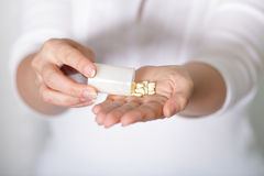 Pilling pills onto hand Stock Images