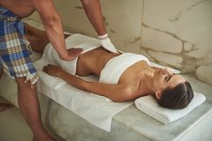 Caring man doing kese pilling to the relaxed lady in hammam stock images