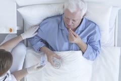 Pillola di presa paziente con bicchiere d'acqua Immagini Stock Libere da Diritti