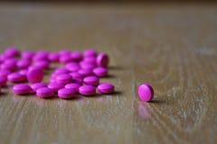 Pillola rosa sullo scrittorio di legno come simbolo del medicinale che contribuisce a curare la malattia Fotografia Stock Libera da Diritti