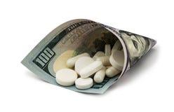 Pillole bianche con soldi Costo della salute molto Immagine Stock Libera da Diritti