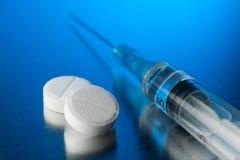 Pillole bianche con una siringa su un fondo blu Fotografia Stock Libera da Diritti