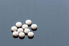 Pillole bianche della medicina isolate su fondo di vetro Fotografie Stock