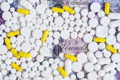 Pillole bianche e gialle su un fondo dei soldi fotografia stock libera da diritti