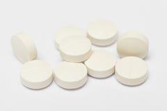 Pillole bianche su priorità bassa bianca Fotografia Stock Libera da Diritti