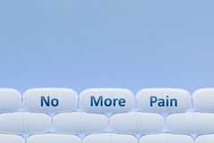 Pillole bianche su un fondo blu con il ` di parole non più ` di dolore Fotografia Stock