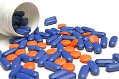 Pillole blu e rosse con la bottiglia Fotografia Stock Libera da Diritti