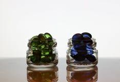 Pillole blu e verdi in barattoli di vetro, granelli fotografie stock