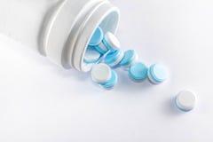Pillole blu una bottiglia di pillola su fondo bianco Fotografie Stock