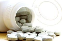 Pillole che cadono da una bottiglia Immagini Stock Libere da Diritti
