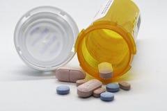 Pillole che rovesciano fuori una bottiglia della medicina immagine stock