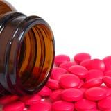 Pillole che si rovesciano da una bottiglia di pillola isolata su bianco Immagini Stock Libere da Diritti