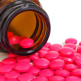 Pillole che si rovesciano da una bottiglia di pillola isolata su bianco Immagine Stock Libera da Diritti