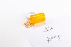 Pillole che si rovesciano dalla bottiglia della medicina con sono nota spiacente, dose eccessiva di suicidio dell'implicazione Immagini Stock Libere da Diritti