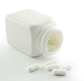 Pillole che si rovesciano dalla bottiglia di pillola Immagine Stock