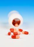 Pillole che si rovesciano dalla bottiglia di pillola Fotografia Stock Libera da Diritti