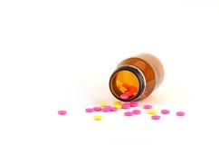 Pillole che si rovesciano dalla bottiglia isolata su bianco Immagini Stock