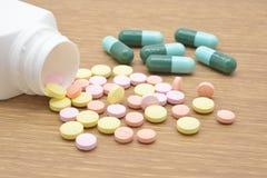 Pillole che si rovesciano fuori Fotografia Stock
