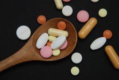Pillole colorate in cucchiaio di legno con una parte di pillole della medicina isolate su fondo nero Concetto della medicina e di Immagini Stock