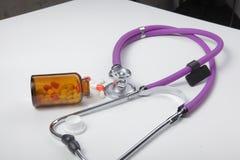 Pillole, compresse e stetoscopio su fondo bianco Fotografie Stock