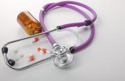 Pillole, compresse e stetoscopio su fondo bianco Fotografia Stock