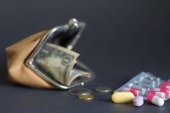 Pillole con un portafoglio di cuoio vuoto su fondo scuro fotografia stock