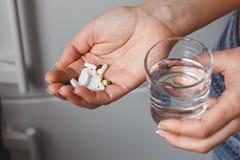Pillole d'offerta della donna e un vetro di acqua pura Concetto di salute Fotografie Stock