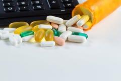 Pillole del farmaco con la bottiglia aperta davanti al calcolatore su briciolo Fotografie Stock Libere da Diritti