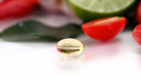 Pillole dell'olio della medicina di erbe su fondo di verdure Fotografie Stock Libere da Diritti