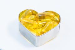 Pillole dell'olio di pesce su cuore isolato Fotografia Stock