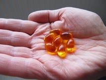 Pillole dell'olio di pesce sulla mano dell'uomo Immagini Stock Libere da Diritti