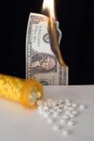 Pillole della bottiglia della medicina che si rovesciano fuori sul burning dei soldi e della tabella Fotografia Stock
